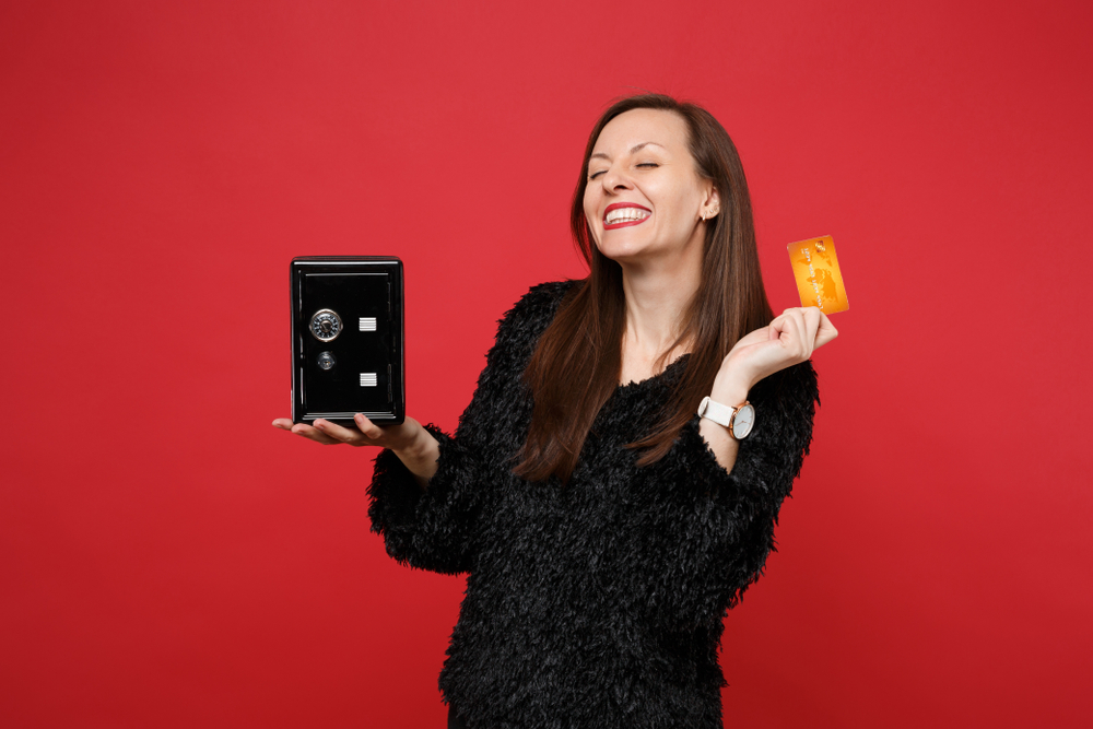 woman happy holding credit card and a small safe representing security