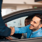 Man shaking hands with car salesman through window
